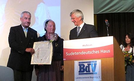 Kultusminister Ludwig Spaenle und Landrat Christian Knauer, Vorsitzender des BDV Bayern, ehren Gerda Graumann für ihr über 50-jähriges Engagement im BDV