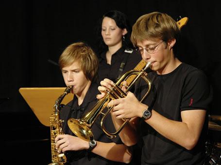 Drei junge Musiker beim Spielen ihrer Instrumente