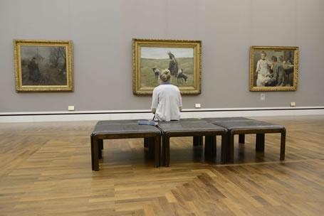 Eine Besucherin genießt Gemälde in der Neuen Pinakothek