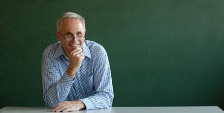 Lehrer lächelnd vor Tafel