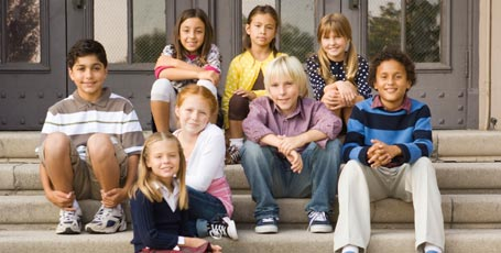 Gruppe Schüler auf der Treppe vor Schule sitzend