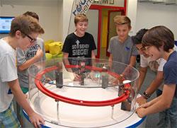 Teamarbeit und viel Fingerspitzengefühl sind gefragt, um am spielerischen Teilchenbeschleuniger eine Kugel in Schwung zu bringen