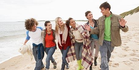 Junge Leute spazieren am Meer