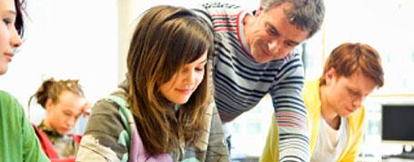 Ein Lehrer erklärt einer Schülerin den Lernstoff