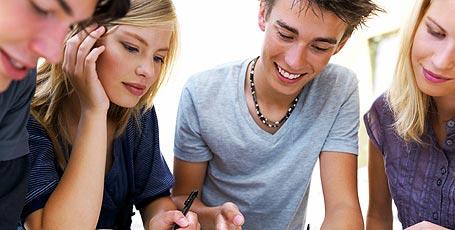 4 Schüler arbeiten gemeinsam an einem Tisch