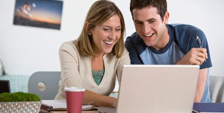Mann und Frau lachend vor Laptop