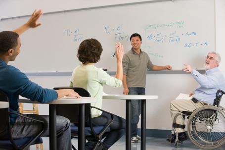 Lehrer im Rollstuhl unterrichtet mit Assistent Schüler