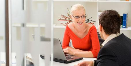 Frau vor Laptop mit Mann sprechend
