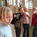 Gruppe von Schüler/innen beim Hänseln eine Mitschülerin