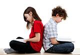 Zwei Kinder sitzen Rücken an Rücken und lesen