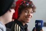 ein Schüler mit Mütze blickt in die Kamera