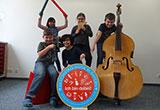 Schüler zeigen das Schild des Aktionstages Musik in Bayern