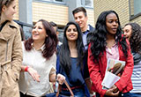 Schüler mit Migrationshintergrund vor einer Schule