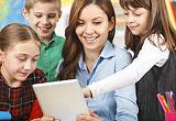 Lehrerin mit Schülern vor einem Tablet