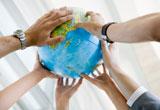 Viele Hände halten eine Weltkugel