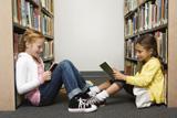 Zwei Mädchen lesen Bücher in einer Bibliothek auf dem Boden sitzend.