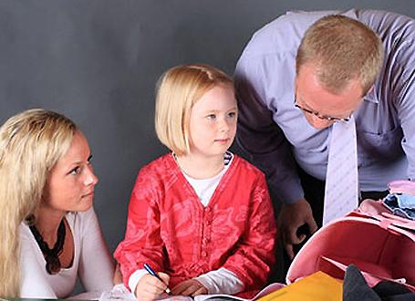 Grundschülerin mit Lehrer und Mutter