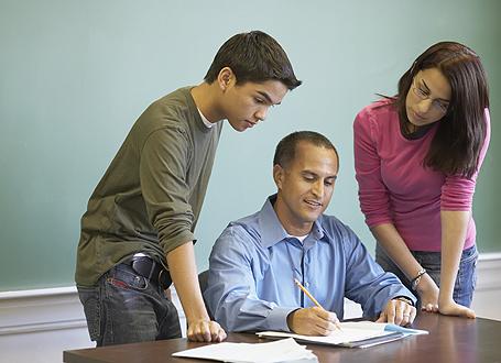 Zwei Schüler stehen neben ihrem sitzenden Lehrer