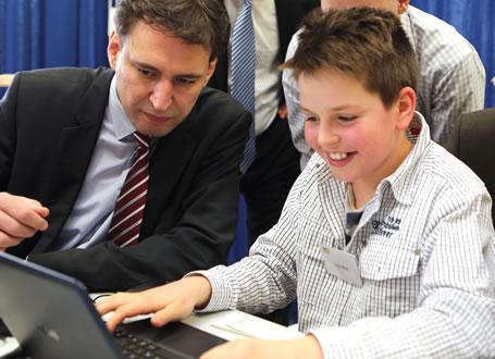 Bildungsstaatssekretär Georg Eisenreich verfolgt aufmerksam wie ein Schüler mit lernreich 2.0 arbeitet