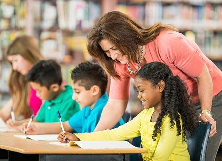 Lehrerin mit Schülerinnen und Schülern mit Migrationshintergrund
