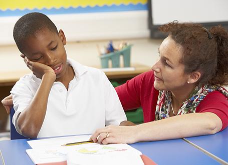 Lehrerin mit Flüchtlingsjungen im Unterricht