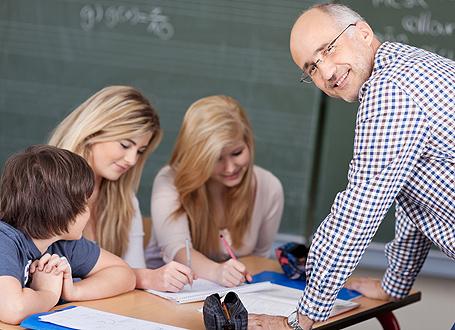 Lehrer unterstützt drei Schüler bei einer Aufgabe